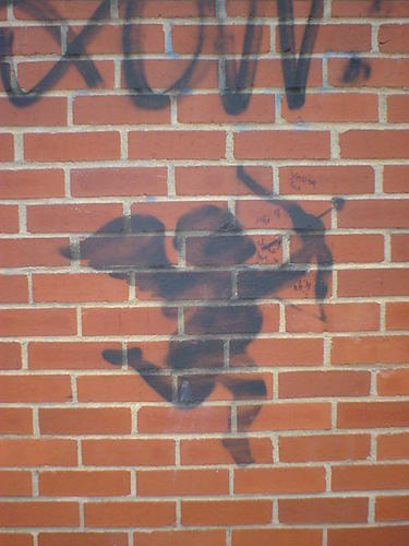 Silhouette of Cupid with bow, stencilled on a brick wall