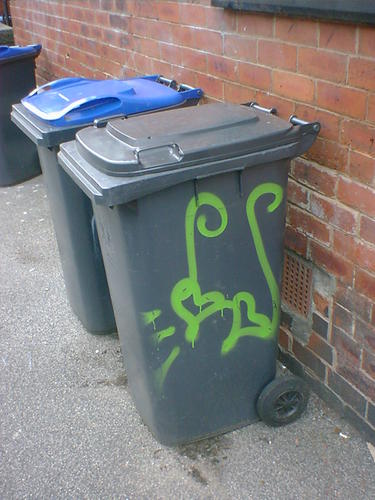 A wheelie bin with green hearts painted on.
