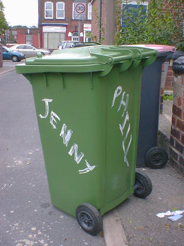 Green wheelie bin with Jenny and Phill daubed on two sides with white paint.