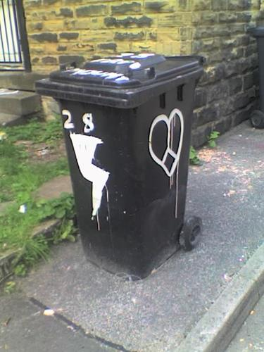 A wheelie bin painted with a lightning bolt on one side and a heart on another.
