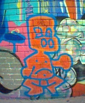 Graffiti art - a red-orange boy, outlined in blue, with big nostrils.