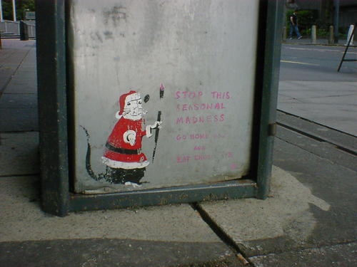 Small painting of a rat, dressed as Santa, at the base of a dustbin in Leeds.