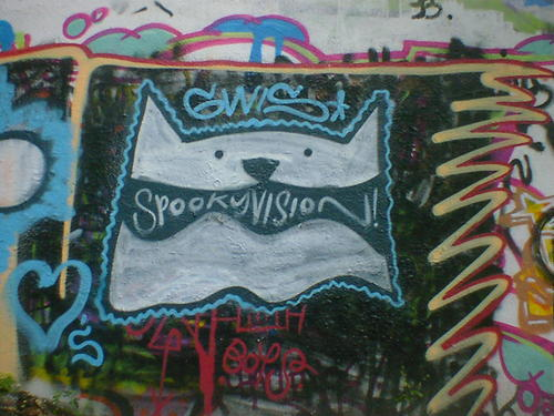 Graffiti of a dog, with spooky vision written inside the mouth.
