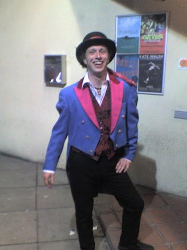 Andrew poses in a bright blue tailcoat, with hot pink lapels, and a bowler hat.