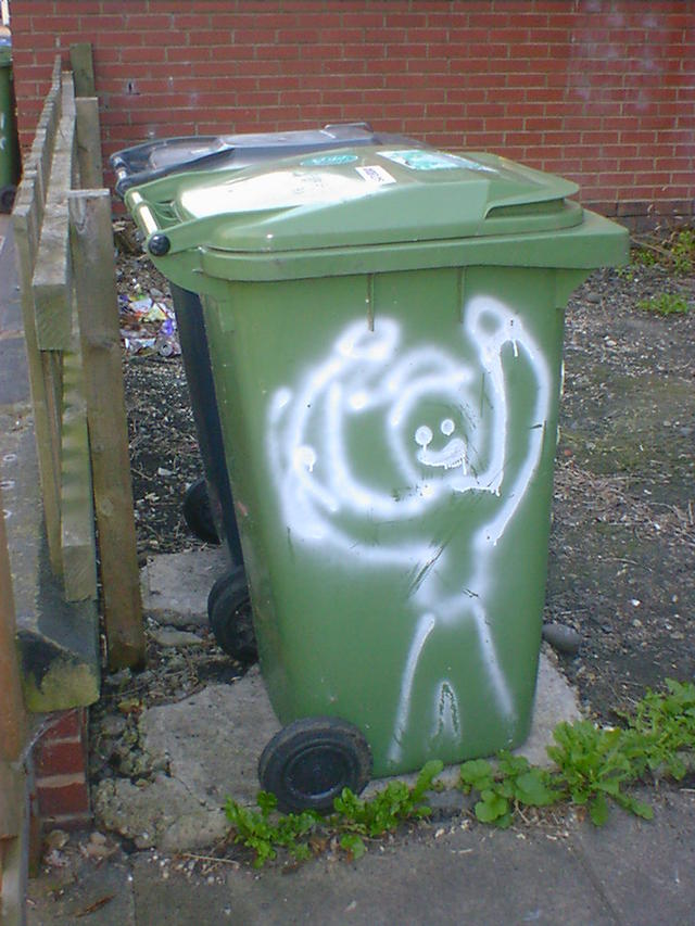 A grinning man painted on a wheelie bin, holding his arms high in victory.