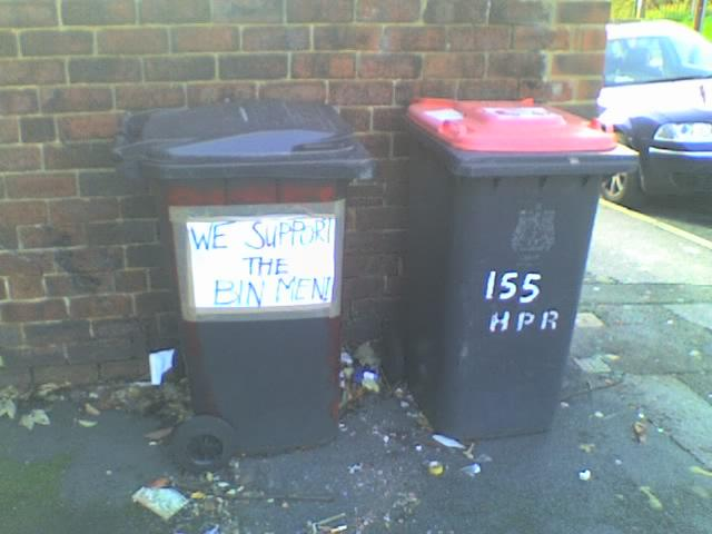 a sign affixed to a wheelie bin declares: we support the bin men