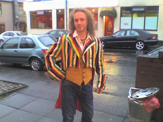 Andrew poses in a multi-coloured stripey tailcoat, hand on hip.