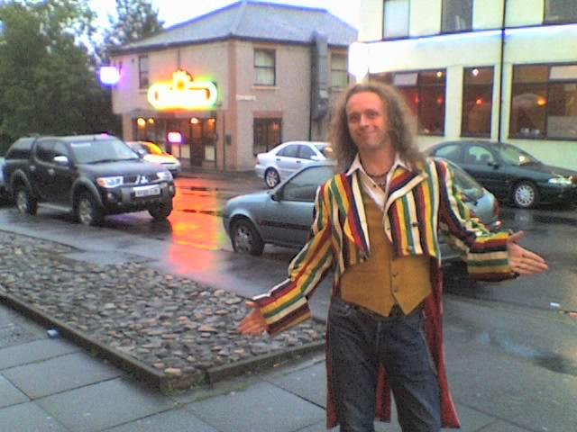 Andrew poses in a multi-coloured stripey tailcoat, with open arms