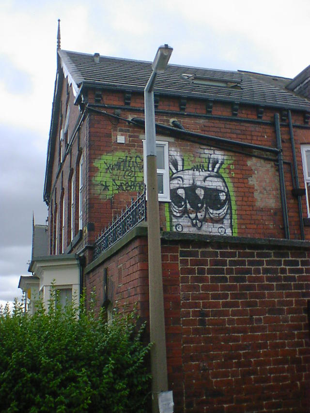 Green rabbit graffiti, on the upper storey of a red-brick terraced house.