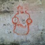 graffiti on decaying wall, a googley-eyed face resembling Admiral Akbar