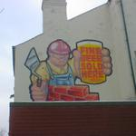 A cheerful cartoon-style bricklayer, holding a pint. Fine beer sold here.