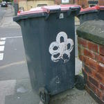 A five-petalled flower painted on a wheelie bin.