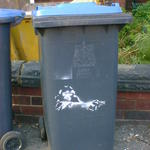 Stencil art on a wheelie bin. A monkey aiming a revolver, cop-show style.