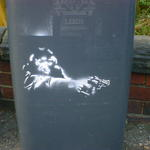 Stencil art on a wheelie bin. A monkey aiming a revolver, cop-show style