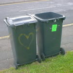 Two wheelie bins standing close together. One has a heart spray-painted on it.