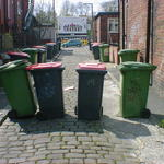 Four wheelie bins standing spread across a back alley, casting long shadows.