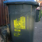 Wheelie bin with stencil art of a mob uprising, advertising Attila Bike Parts.