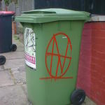 A red monogram spray-painted on a green wheelie bin.