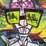 Graffiti art - a bald scientist with big green spectacles. The lenses say HA HA.